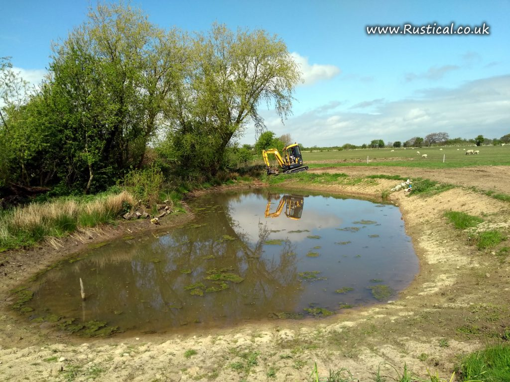 Using a digger to raise the pond water level